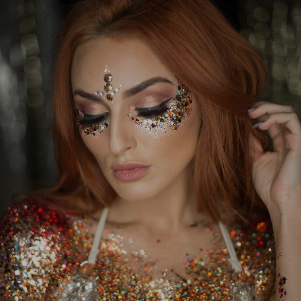 orange body and face glitter worn by a woman with orange hair