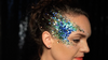 woman wearing blue glitter on her face and into her hair