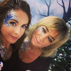 two women wearing blue glitter on their faces