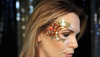 woman wearing orange and yellow face glitter in her hair