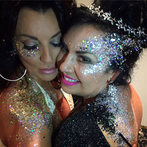 two women wearing silver glitter on their faces and in their hear