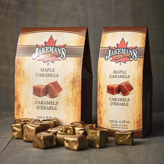 Two boxes of Jakeman's Maple Caramels with caramels scattered around them.