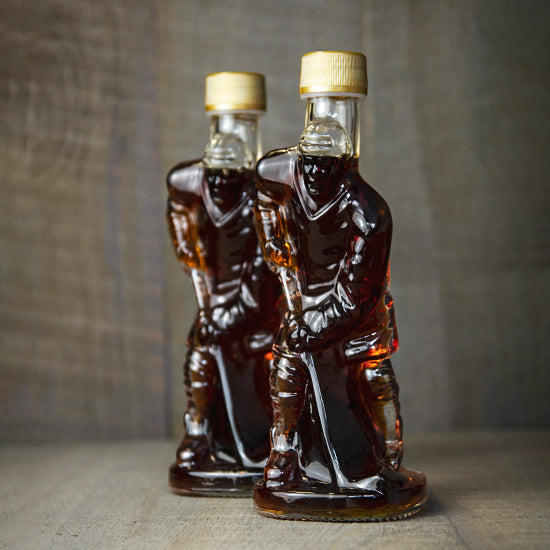 Two of Jakeman's glass hockey player bottles with their Pure Maple Syrup.