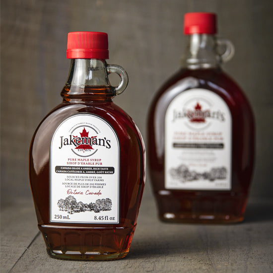 Two glass kent bottles of Jakeman's Maple Syrup.