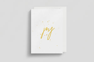 "Simple Christmas card design with the word ""Joy"" printed in the middle of the card and gold colour splattering"