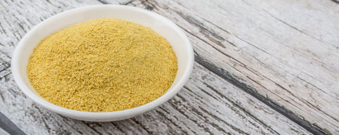 Yellow nutritional yeast in a white bowl