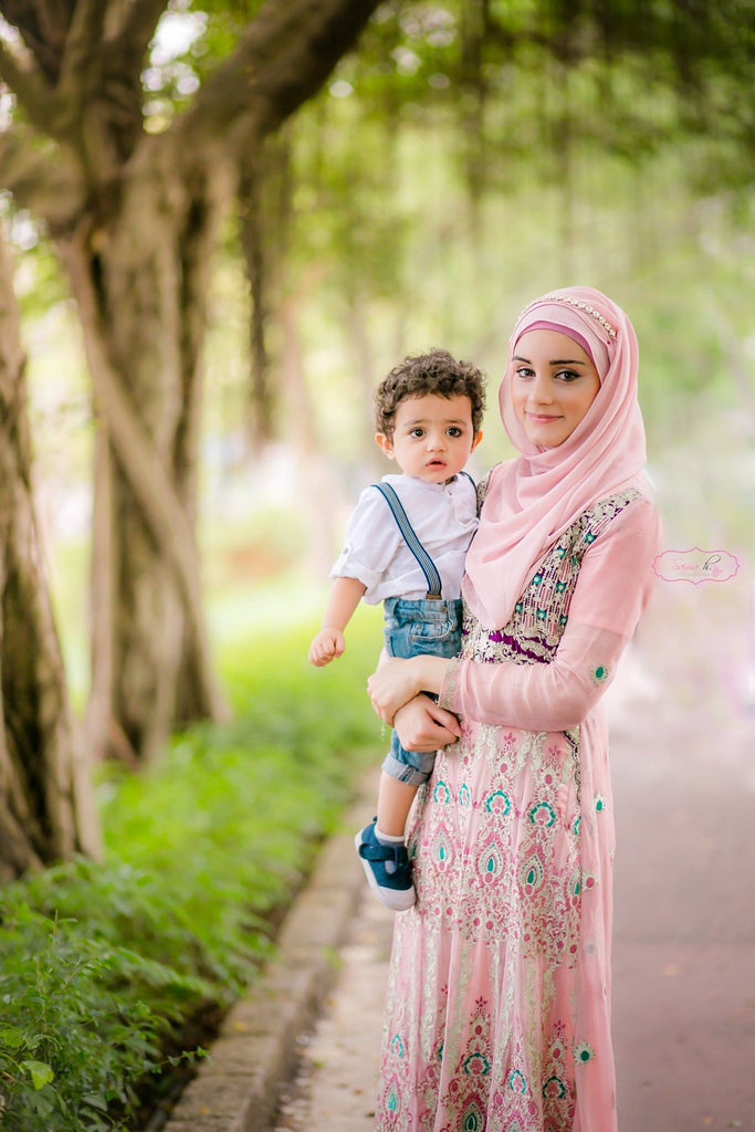 Mom holding her young son in her arms with a bokeh background