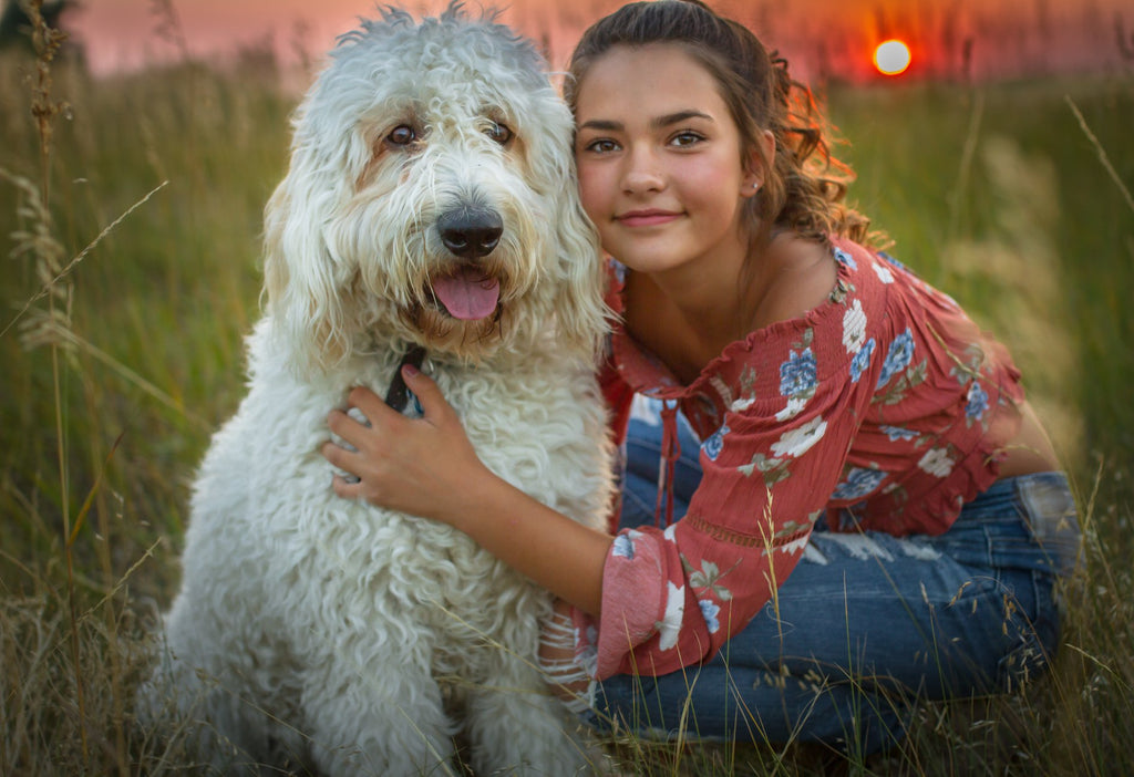 Portrait photo of girl and labradoodle dog