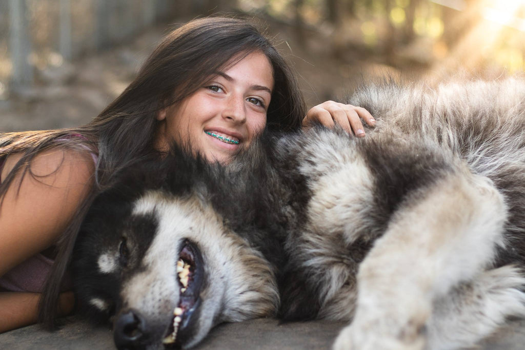 Photo of Girl and dog laying on ground and smiling