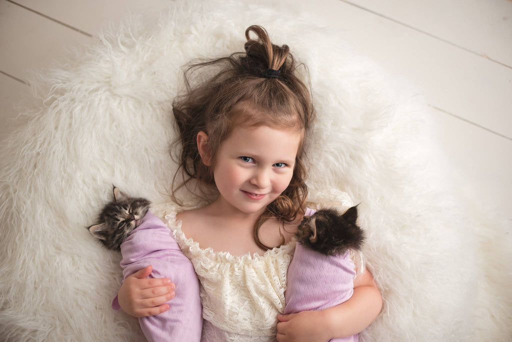 Girl holding two kittens