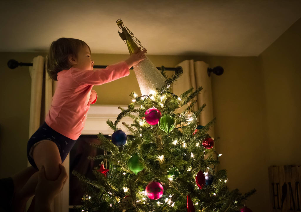 Photo of Girl Placing Angel on Top of Christmas Tree