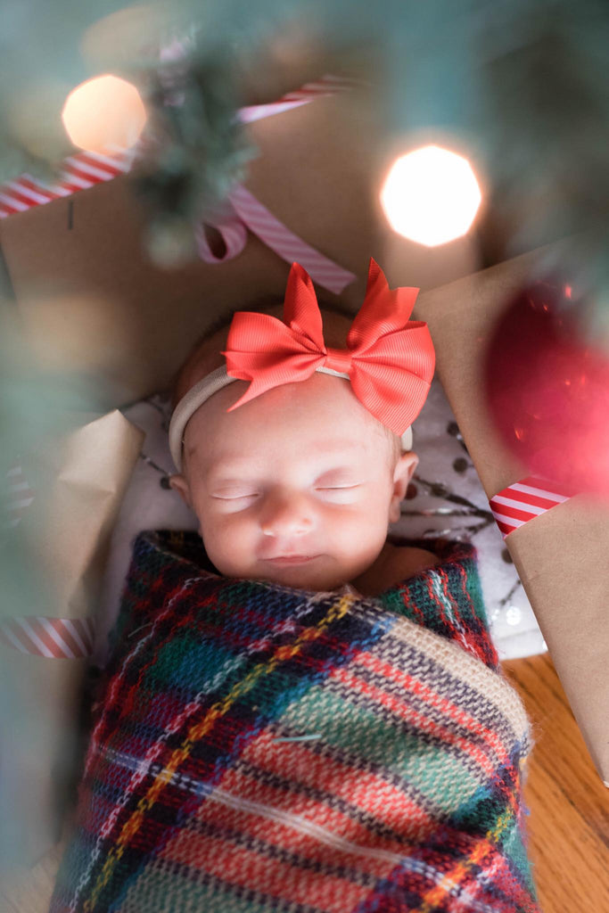 Photo of Infant Framed by Christmas Tree Branches