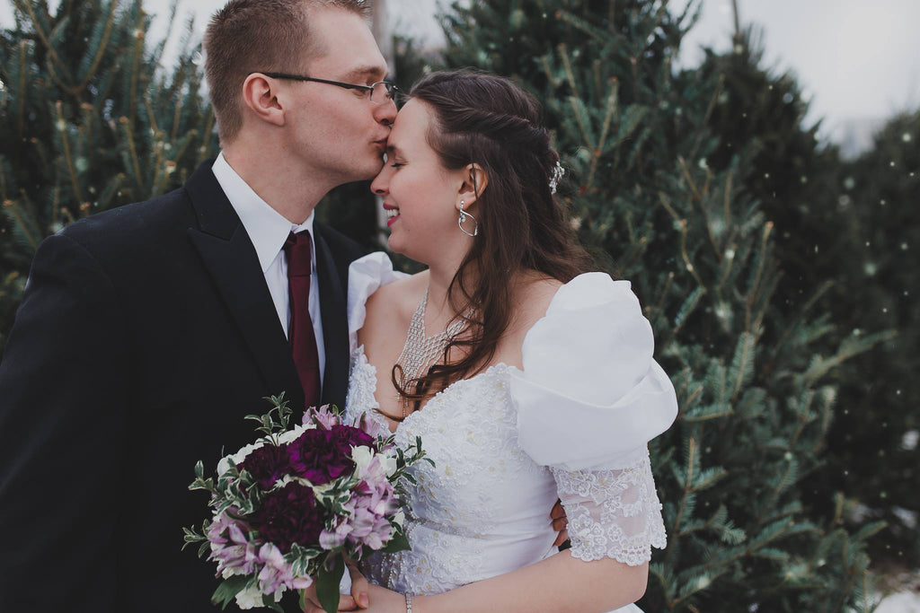 Wedding Photo of Couple Kissing in Front of Christmas Trees