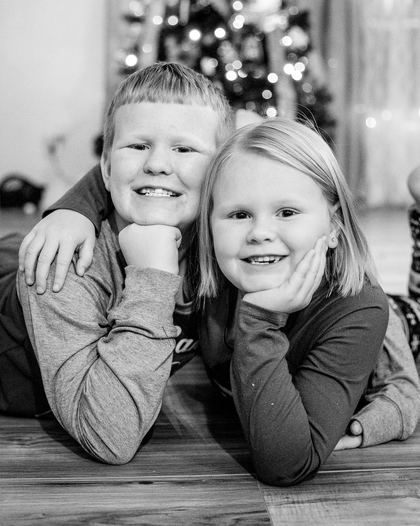 Portrait Photo of Kids Smiling in Front of Christmas Tree
