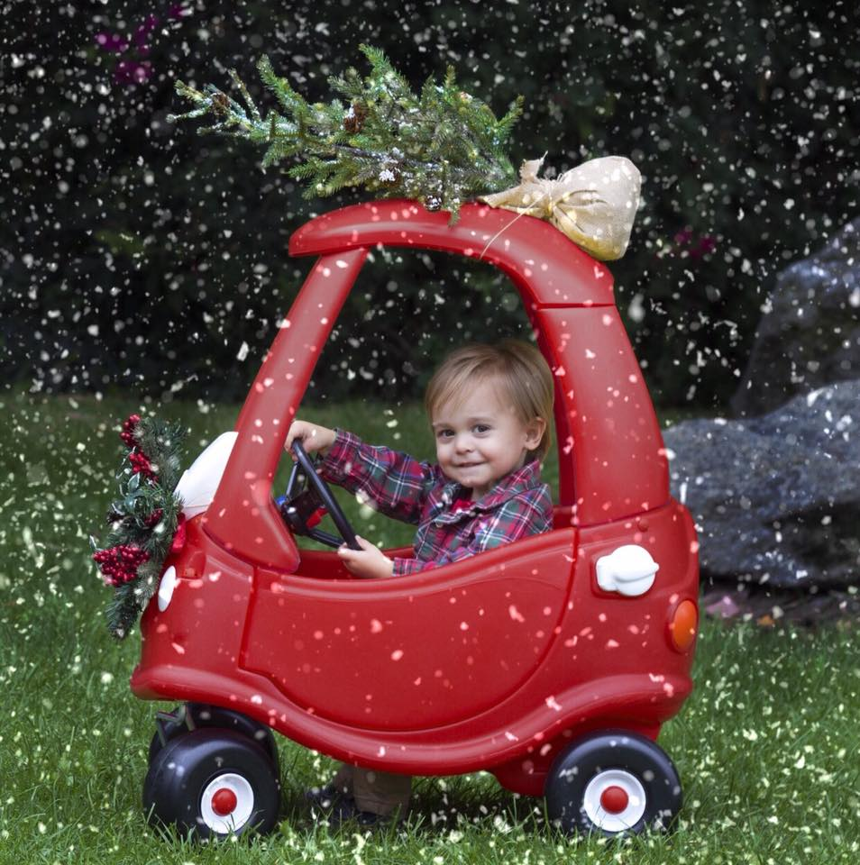 Child Driving Toy Car with Christmas Tree on Top