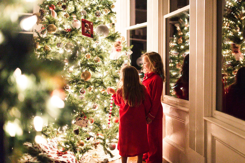 Photo of Kids hanging ornaments on Christmas Tree