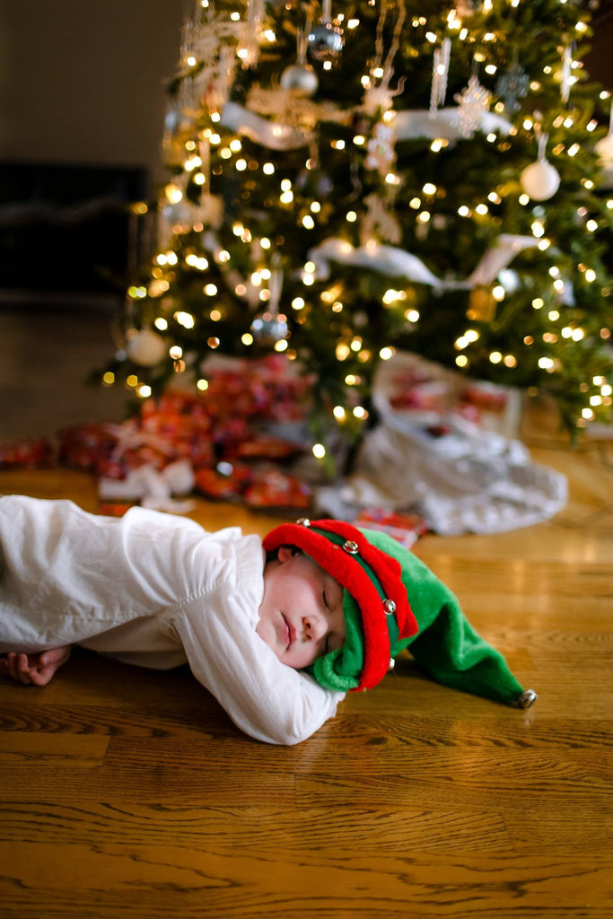 Photo of Child Sleeping in Front of Christmas Tree