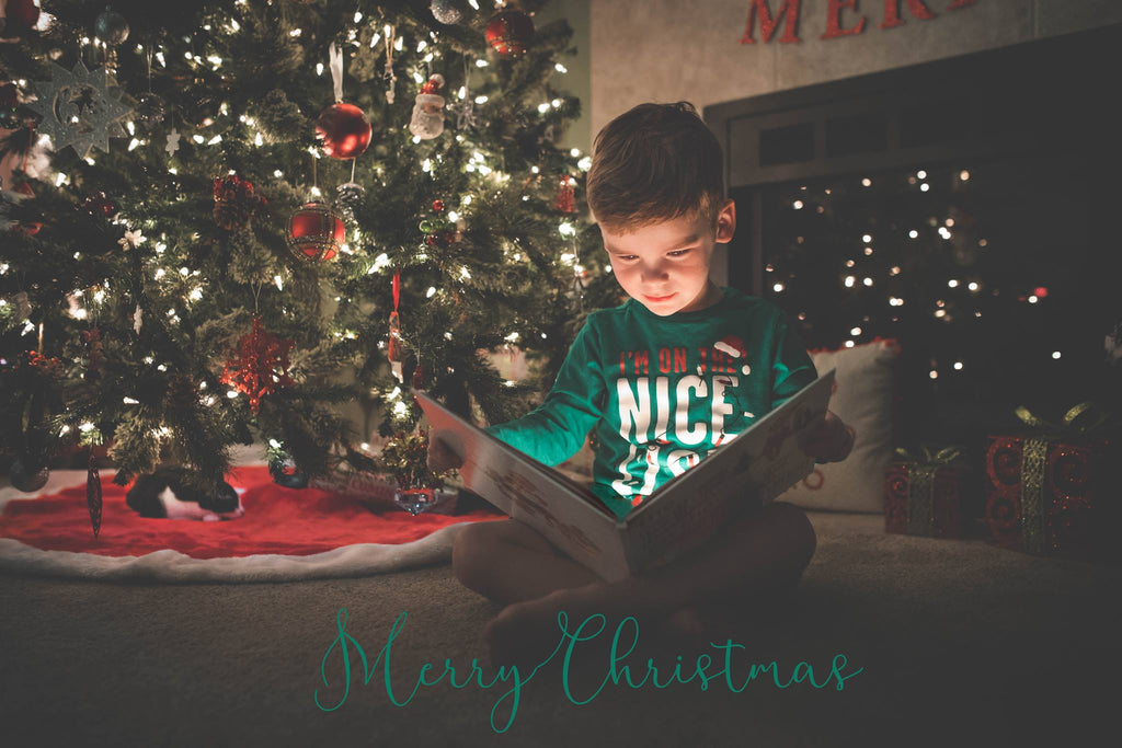 Child Reading Magical Storybook in Front of Christmas tree