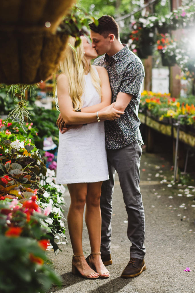 Spring photo of couple kissing in greenhouse