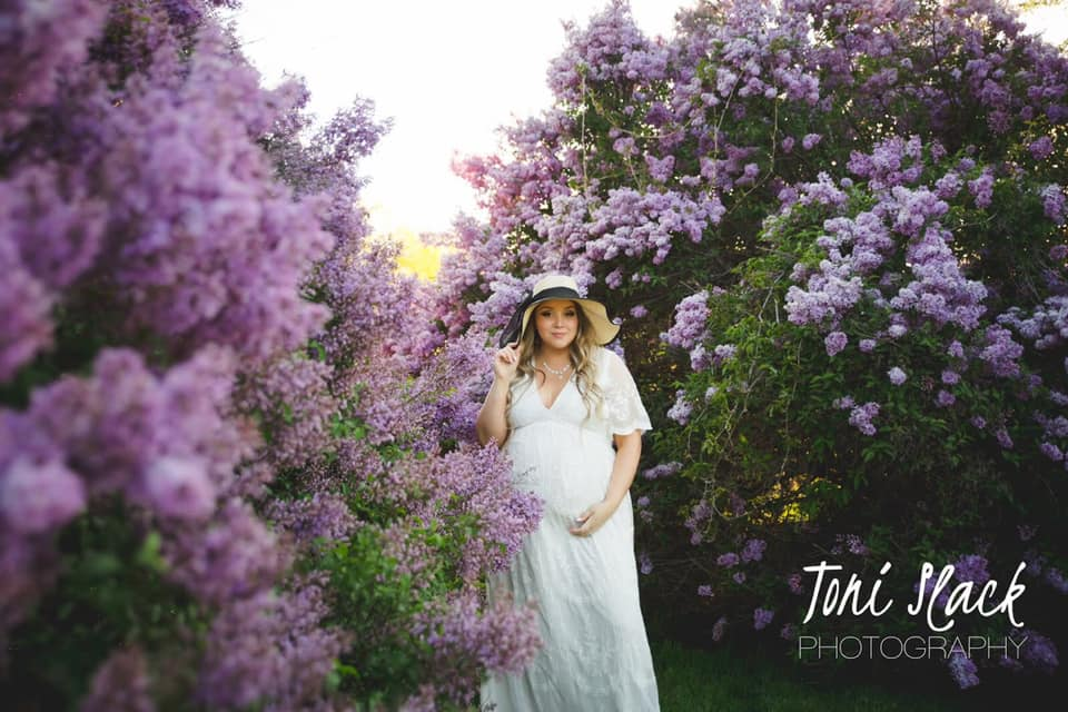 Maternity image posing in spring blossoms