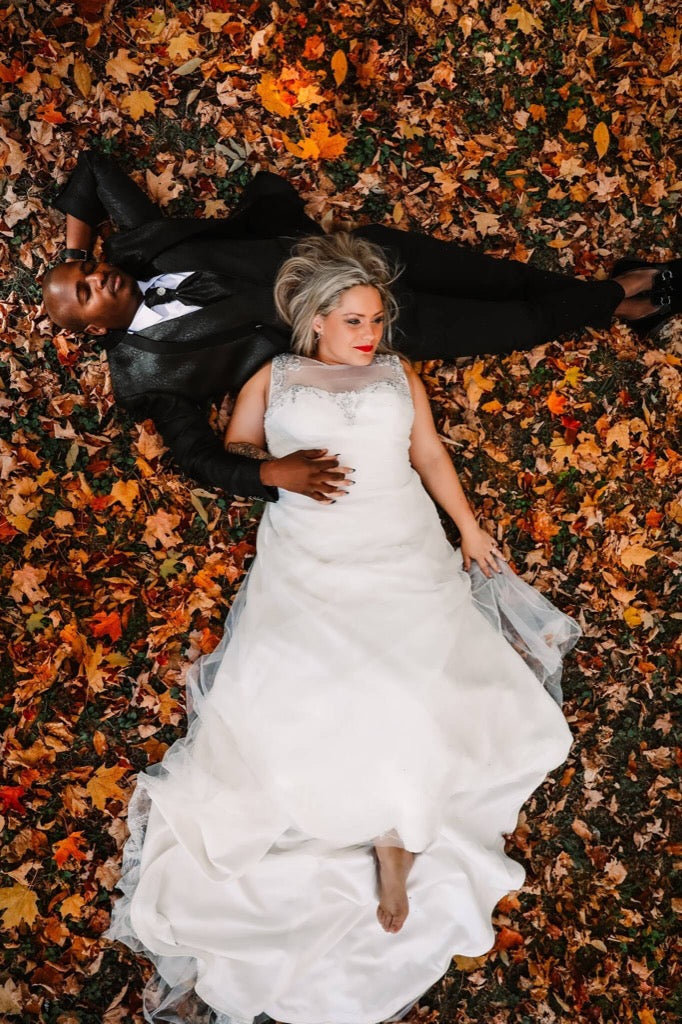 best photos 2019 - bride and groom laying down in fall leaves