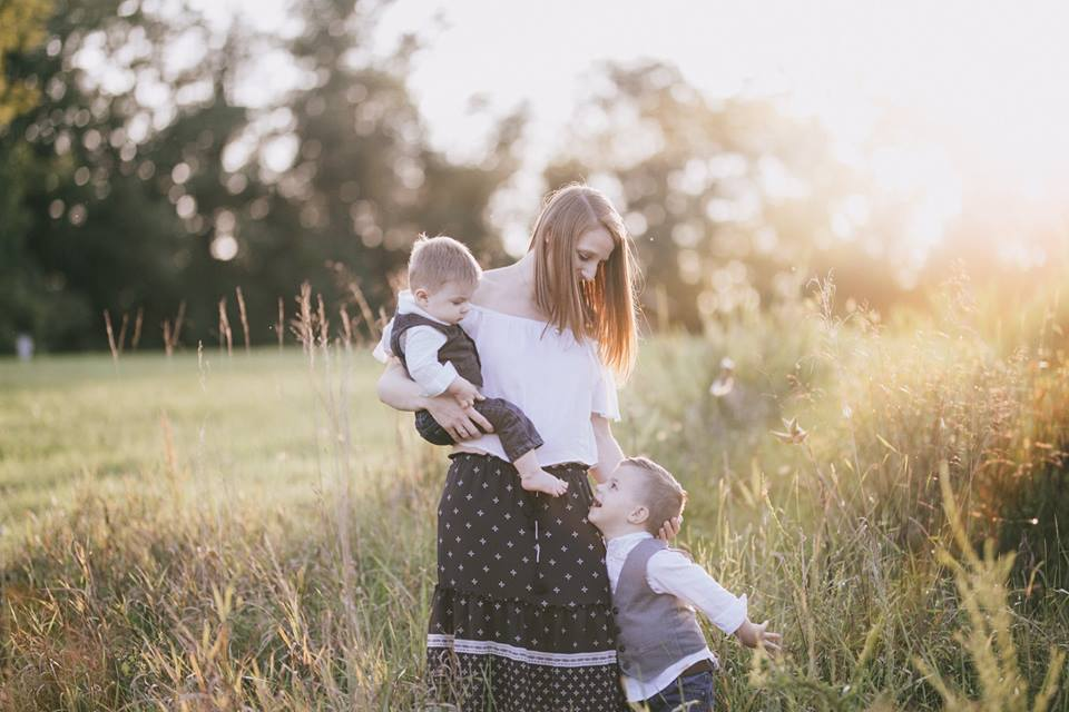 Family Image of Mother with two sons in a field at sunset