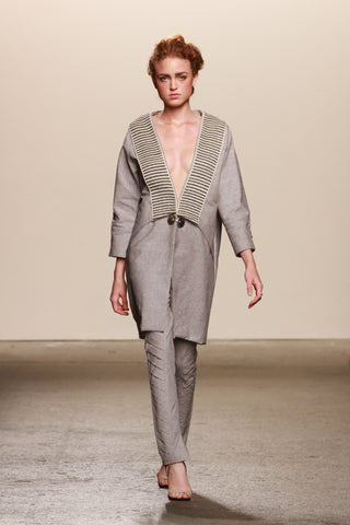 Look 23: Theresa, Lineas Coat in stone organic cotton with hand-loomed pima cotton and alpaca textile, Mapuche handmade artisanal broche and buttons, Razer Pants in stone cotton