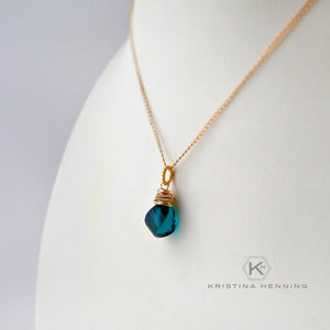 gold necklace with blue green gemstone pendant