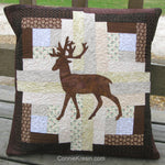 Appliqued deer on a log cabin quilt pillow