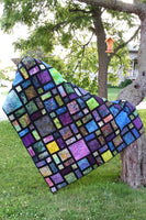 Scattered quilt pattern is fast and easy to make using black at the sashing for the blocks
