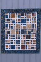 Scattered quilt pattern is fast and easy to make using creat at the sashing and bold browns and navy batiks for the blocks