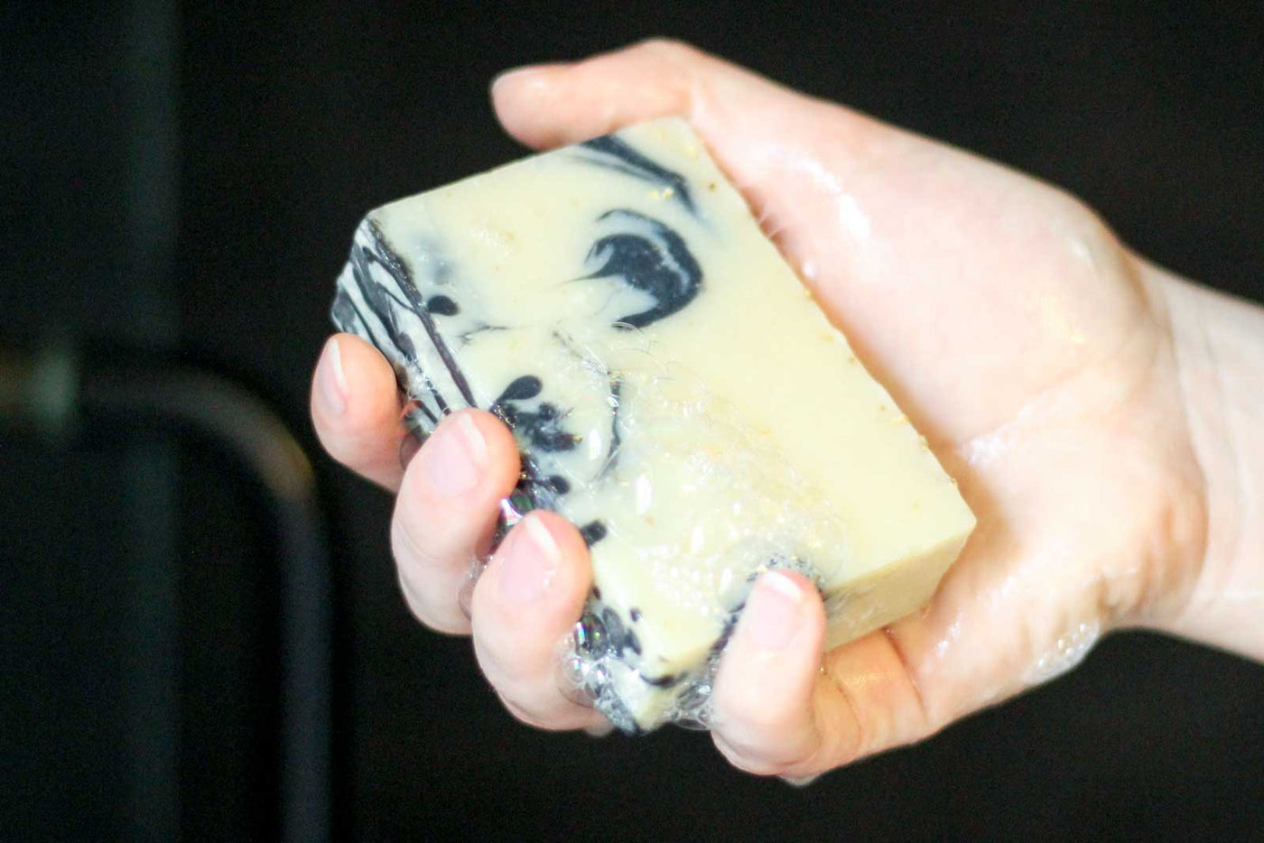 A wet hand holds a sudsy soap bar with black charcoal swirls