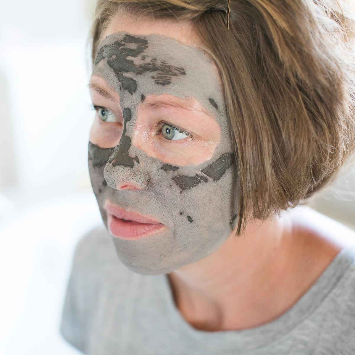 A clay mask begins to dry on a woman's face