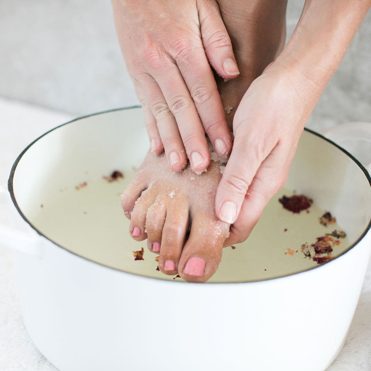 A woman rubs Sugar Scrub into her feet over a tub of water