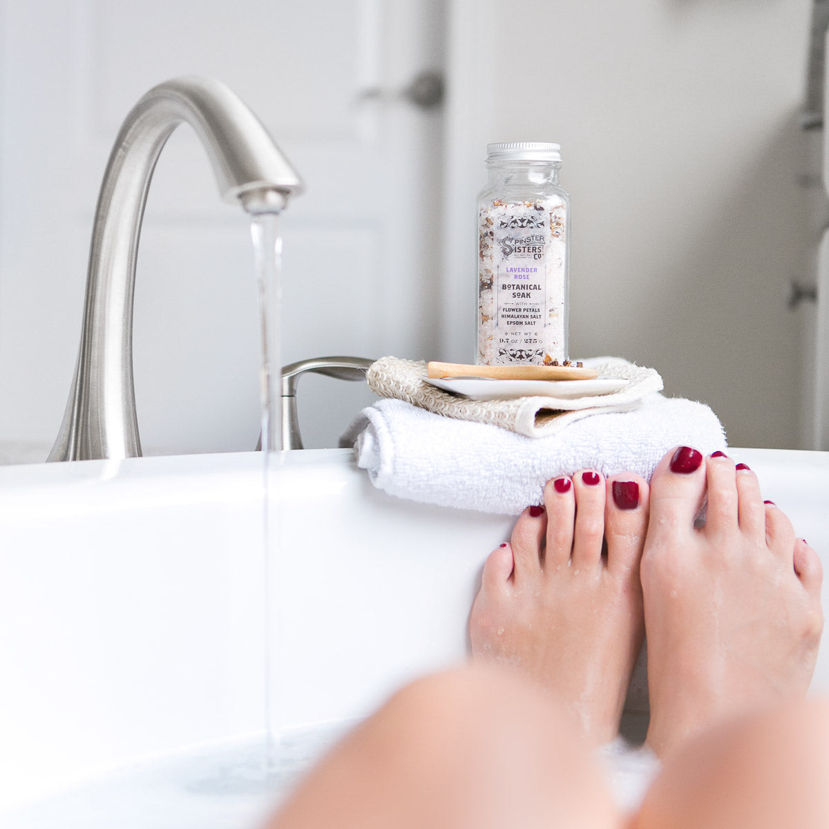A woman puts her feet up in the tub with a bottle of Lavender Rose Botanical Soak sitting nearby