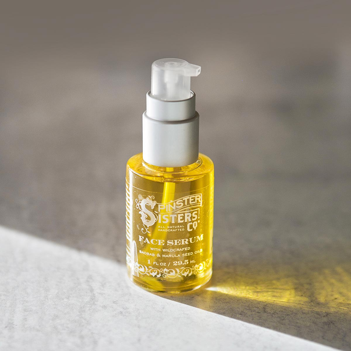 Bright yellow face serum in clear bottle on table