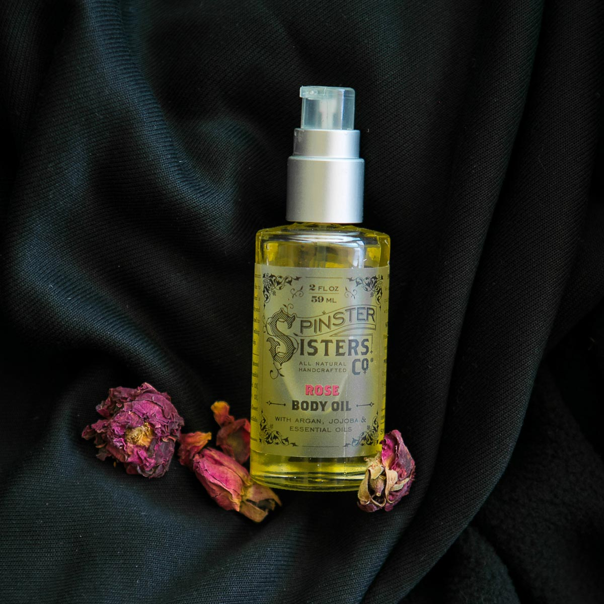 A clear bottle of yellow-hued Body Oil styled with dried rose petals