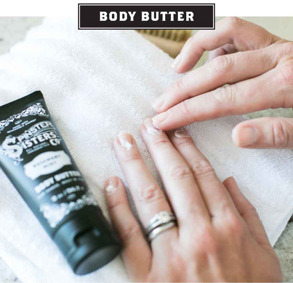 A woman applies Body Butter from a tube to her cuticles