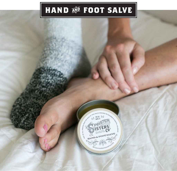 A woman in bed puts heavy socks over her feet after rubbing in salve
