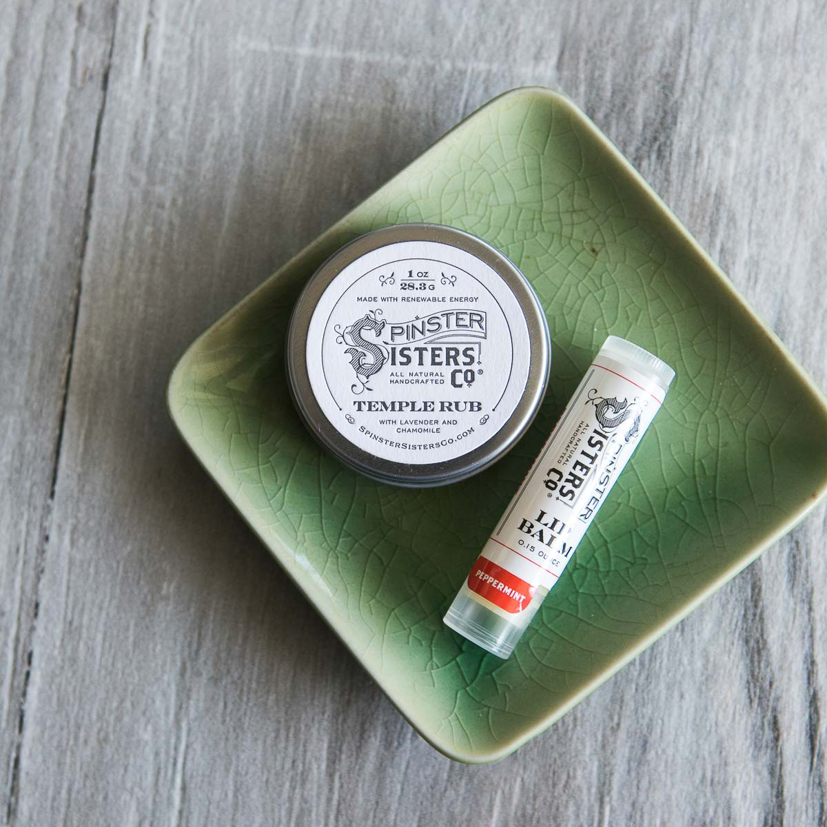 A tin of Temple Rub sits in a tray next to a tube of Peppermint Lip Balm