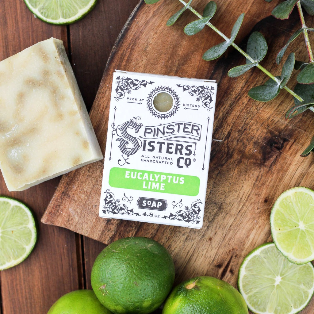 A Eucalyptus Lime soap bar surrounded by fresh limes