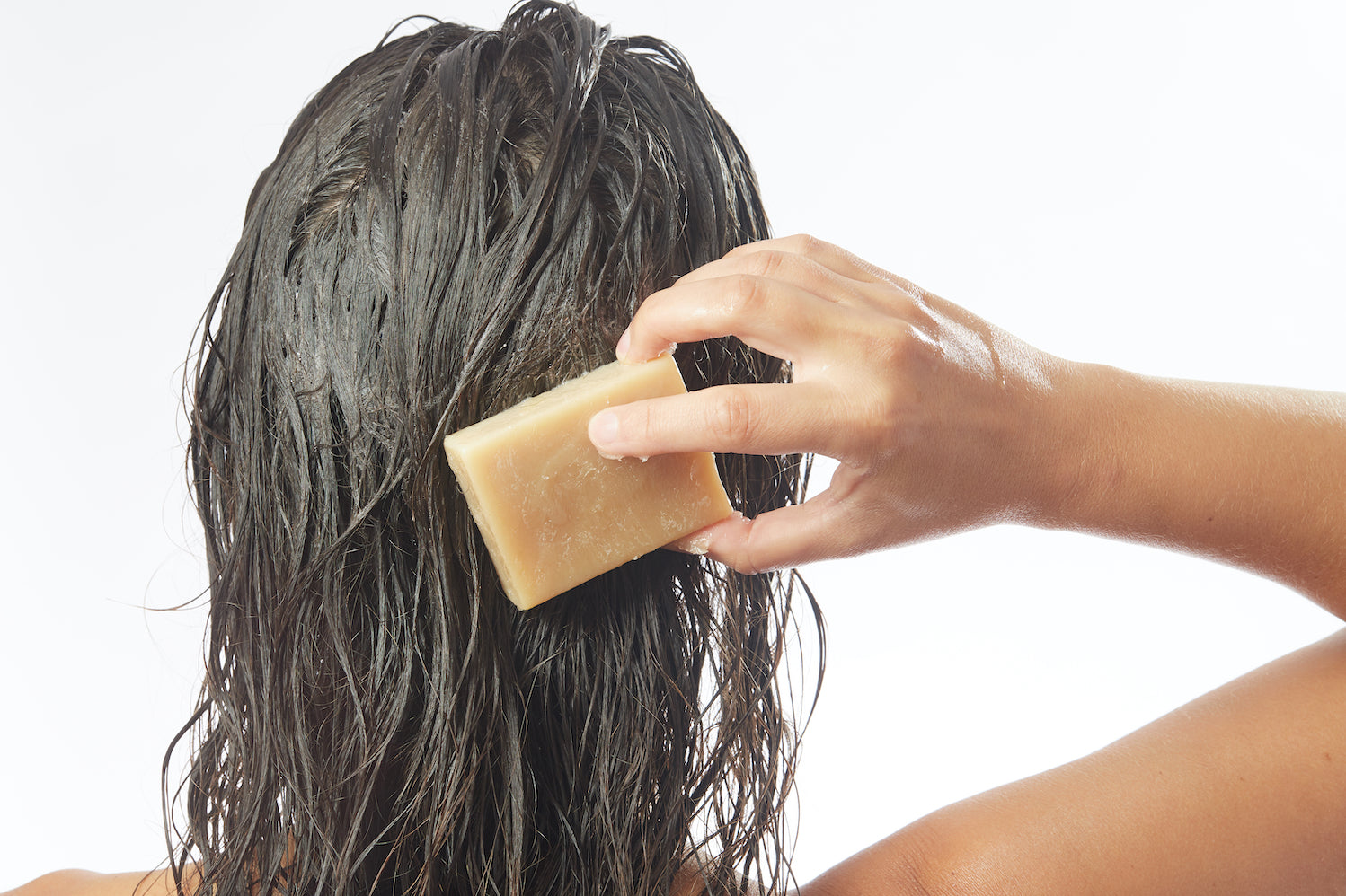 woman rubbing a bar of shampoo on her wet brown hair