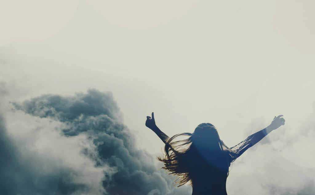 a woman in silhouette in front of a cloudy sky with raised arms looking accomplished