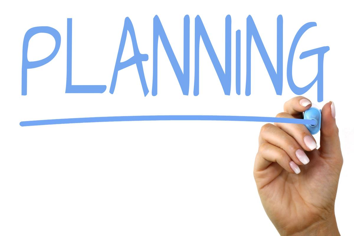Hand writing the word 'planning'