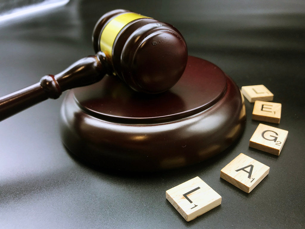 A judge's gavel next to scrabble tiles spelling the word 'legal'