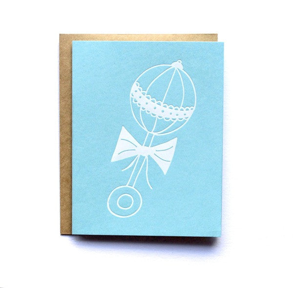 Stock photo of blue cover stock card with white baby rattle screen printed on the front