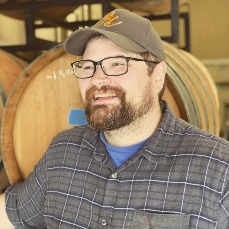 Stan Tomson Assistant Winemaker Smiling Barrels