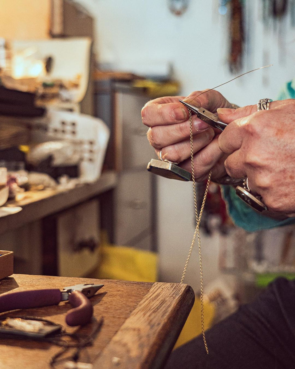 jewellery maker Carole behind the scenes in her brixton jewellery shop and workshop adorned in her own statement rings