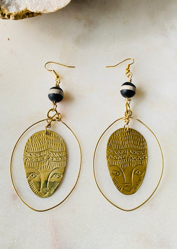 Brass earrings with face in the middle
