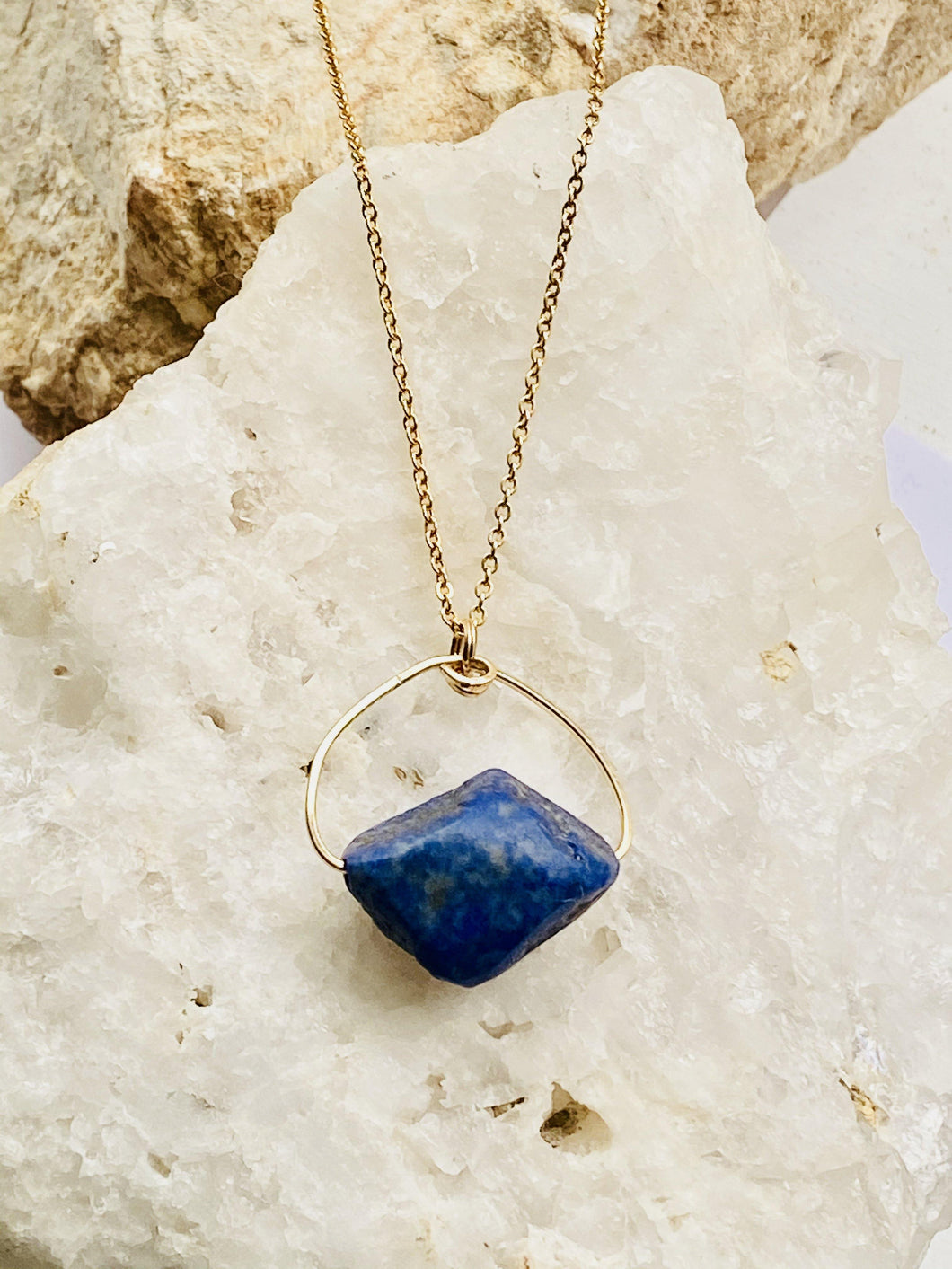 asymmetric natural deep blue stone held on gold plated chain, a handmade bespoke necklace by full moon designs jewellery